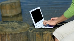 Female hands typing on laptop on wooden stump by the water HD Stock Footage