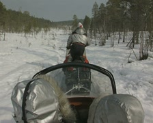 Snowmobile tows passengers in a sled Stock Footage
