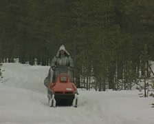 Snowmobile towing a sled heads past the camera Stock Footage