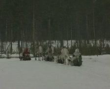 Reindeer pull sleighs across a snowy landscape Stock Footage