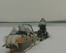 Snowmobile towing a sled across a frozen snowy landscape Stock Footage