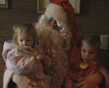 Stock Video Footage of Two Children sit on the lap of Santa Claus
