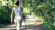 Stock Video Footage of Woman nordic walking in the park, forest, slow motion, dolly shot HD