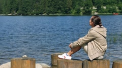 Pensive thinking woman sitting on wooden stump by the lake, dolly shot - stock footage