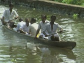 Stock Video Footage of Goa / Cochin A group of Indian men travel down a canal in a wooden dugout canoe