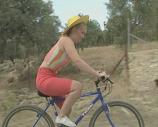 Travelling shot of woman and man cycling through country Stock Footage