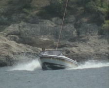 Pan up from person driving speedboat to parasailer being towed by boat Stock Footage