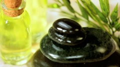 Black Spa Stones, Oils & Green Leaves in Close up Stock Footage