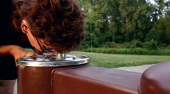 Woman drinking from water fountain dolly shot Stock Footage