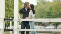 Love with romantic boyfriend and girlfriend kissing on bridge Stock Footage