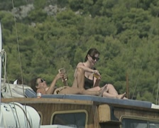 Close up of couple lying on boat reading and applying sunscreen Stock Footage