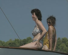 Close up of women sitting on edge of travelling boat Stock Footage
