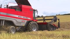 Red combine harvester starting to cut a row of rape seed Stock Footage