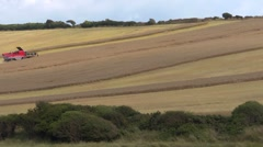Combine harvester cutting a field of rape on a hill in the distance - TL Stock Footage