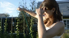 Young woman watering garden and squinting against the sun Stock Footage