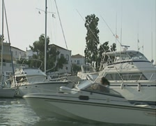 Travelling past yachts and motor boats off the coast of the island of Spetses Stock Footage