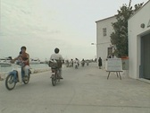 View of waterfront road and motorcycles passing Stock Footage