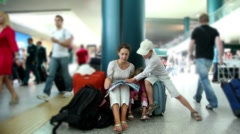 Mother and kids sit in airport and reading book - stock footage
