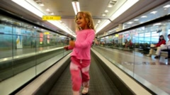 Little girl goes on automatic track in the airport Stock Footage