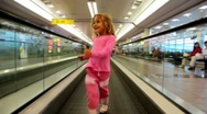Stock Video Footage of Little girl goes on automatic track in the airport
