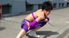 Woman make dance performance with chain, at pavement Stock Footage