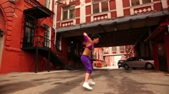 Woman dance active at city lane between houses Stock Footage