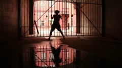 Young woman performs modern dance near lattice gate Stock Footage