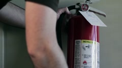 Man grabs and then replaces fire extinguisher closeup Stock Footage