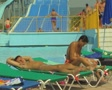 People on sunloungers with waterslide in background Footage