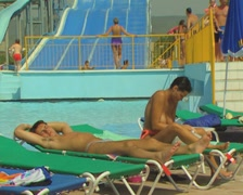 People on sunloungers with waterslide in background Stock Footage