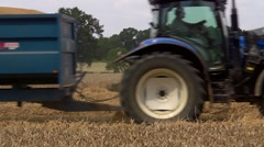 Tractor with trailer full of grain passing the camera full frame L-R Stock Footage