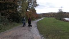 Ladies with pushchairs walking on country path Stock Footage