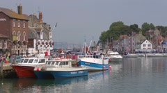 The old harbour and waterfront at Weymouth, Dorset with sailboat moving - stock footage