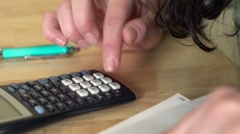 Female using calculator at table Stock Footage