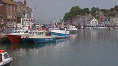 The old harbour and waterfront at Weymouth. Fishing boat going past Stock Footage