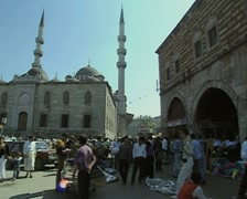 People walking by outside a mosque as prayer call plays Stock Footage