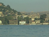 View across river of buildings and passing boat Stock Footage