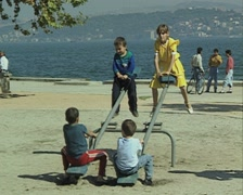 Children playing on see-saw by river Stock Footage