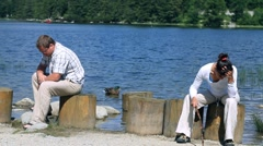 Couple after quarrel sitting on wooden stump by the lake Stock Footage