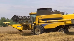 Yellow combine harvester turning to start a new row of wheat Stock Footage
