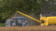 Yellow combine harvester loading wheat into a laden trailer Stock Footage