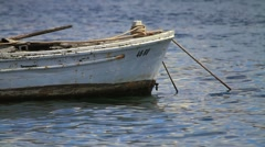 Small fishing boat floating on the water surface Stock Footage