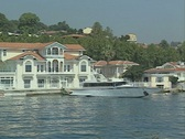View passing riverside house with yacht Stock Footage
