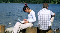 Couple after quarrel sitting by the lake, woman chatting on laptop Stock Footage