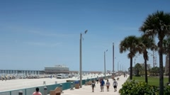 People walking the ocean walk along Daytona Beach with Pier in background Stock Footage
