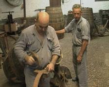 Metalworker hammering at barrel ring Stock Footage