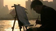 Chinese artist paints skyline at sunset - stock footage