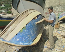 Man breaking wood off upturned small boat Stock Footage