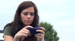 Brunette Female using blue cellphone Stock Footage