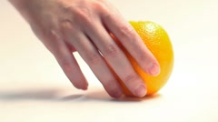 Hand takes an orange on a white background Stock Footage